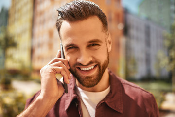 Wall Mural - So good to hear you Portrait of cheerful and handsome bearded man talking by phone and smiling while standing on the street