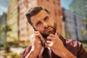 Wall Mural - Hm... Portrait of thoughtful bearded man talking by phone and touching his stubble while standing on the street