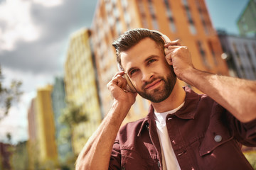 Wall Mural - Best song. Handsome and happy young man with stubble in headphones listening to the music and smiling while standing on the street