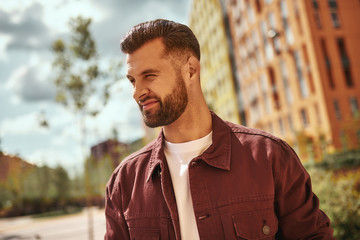 Wall Mural - Perfect weather Portrait of positive attractive man with stubble smiling and looking away while standing on the street