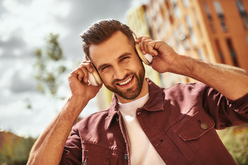 Wall Mural - Can't live without music. Handsome and happy young man with stubble in headphones listening to the music and smiling while standing on the street