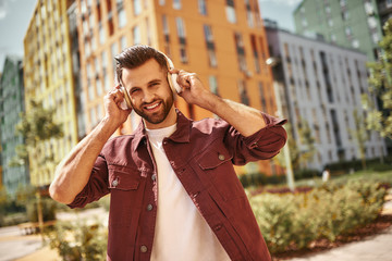 Wall Mural - Good mood. Handsome and happy young man with stubble in headphones listening to the music and smiling while standing on the street