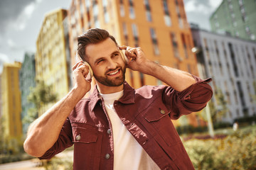 Wall Mural - Happiness. Cheerful young man with stubble in headphones listening to the music and smiling while standing on the street