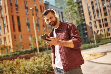 Wall Mural - Next song. Cheerful young man with stubble in headphones listening to the music and holding mobile phone while standing on the street