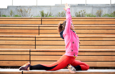 Young woman exercise yoga in the city hands up and balancing standing on one leg in sunny day.
