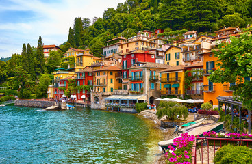 Varenna, Italy. Picturesque town at lake Como. Colourful motley Mediterranean houses on knoll by coastline among green trees. Popular health resort and touristic destination location. Summer day.