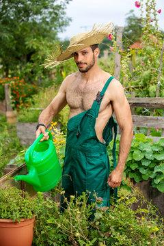 shirtless gardener with straw hat watering flowers