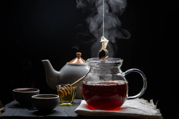Spoed Foto op Canvas Thee Hot tea in a teapot and teacup with steam and tea filter bags on revive the wood and black backdrop.