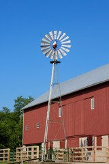 The tall windmill turbine and the red barn in background.
