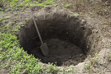 Deep pit in the ground. In the pit lies a shovel. Digging a hole.