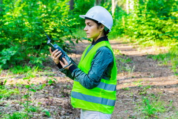 Woman Worker holding Drone Quadcopter for forest inspection Wall mural