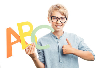 Smiling boy in eyewear with English letters thumb up