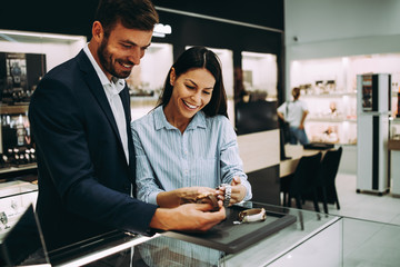 Beautiful couple enjoying in shopping at modern jewelry store.