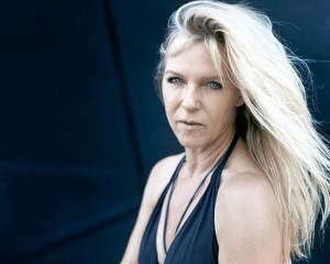 Attraktive reife Frau mit blonden Haaren und  blauen Augen