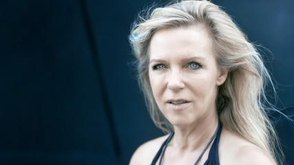 Attraktive reife Frau mit blonden Haaren und strahlend blauen Augen