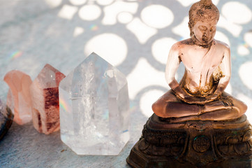 Transluscent pink Buddha statue with healing Reike crystals.