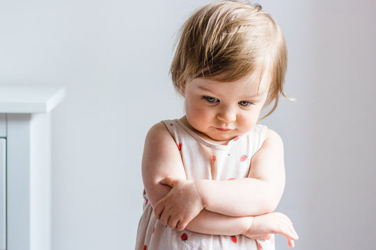 Sad toddler baby girl looking down with her arms crossed