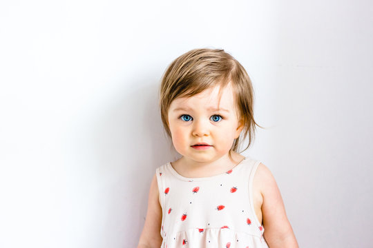 Serious thoughtful attentive child toddler girl against white background
