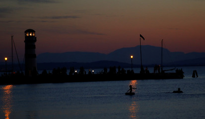 People are seen during sunset at lake Neusiedl in Podersdorf