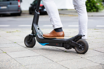 Man With Electric Scooter Standing On Street