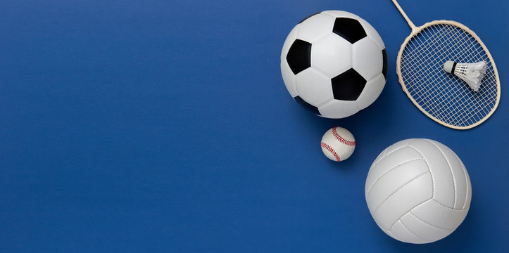 Assorted sports equipment including a basketball, soccer ball, volleyball, baseball, badminton racket on a blue background