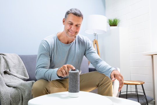Man Pressing Button On Wireless Speaker