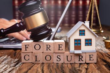 Judge Holding Gavel On House At Desk