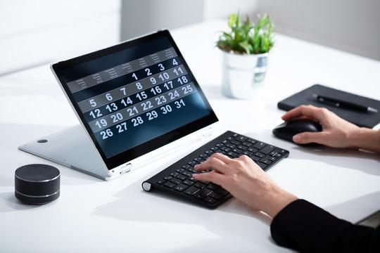 Businesswoman using calendar on laptop