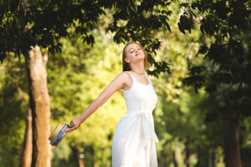 Wall Mural - beautiful girl in white dress holding straw hat while smiling and standing in park with closed eyes