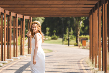 Wall Mural - beautiful girl in white dress touching straw hat while walking near wooden construction and looking at camera
