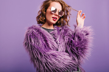 Dreamy pretty girl plays with short curly hair standing on bright background. Indoor portrait of pensive female model in sunglasses and purple fluffy coat. Fotoväggar