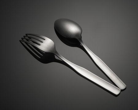 Closeup shot of a metal fork and a spoon isolated on a gray background