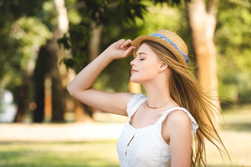 Wall Mural - beautiful young girl in white dress touching straw hat while standing in park with closed eyes