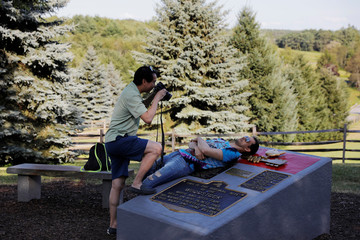 A man photographs another on a memorial near the original site of the Woodstock Music Festival while visiting to celebrate the 50th anniversary of the infamous Woodstock Music Festival in Bethel, New York