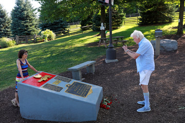 A man photographs his wife at a memorial near the original site of the Woodstock Music Festival while visiting to celebrate the 50th anniversary of the infamous Woodstock Music Festival in Bethel, New York