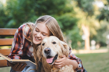 Wall Mural - beautiful girl in casual clothes reading book and hugging golden retriever while sitting on wooden bench in park