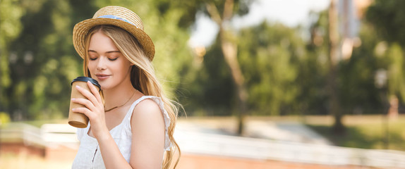 Wall Mural - panoramic shot of beautiful girl in white dress and straw hat holding paper cup and drinking coffee with closed eyes