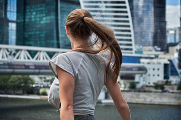 Back view of tourist girl hipster with long hair grows in the wind