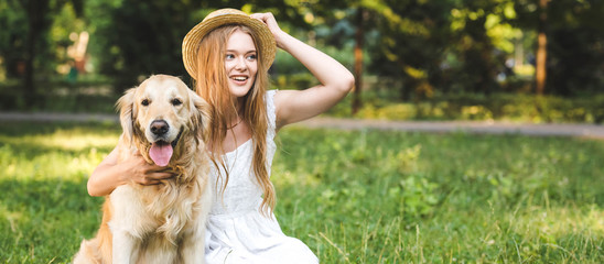 Wall Mural - panoramic shot of beautiful young girl in white dress touching straw hat while hugging golden retriever while smiling, sitting on meadow and looking away