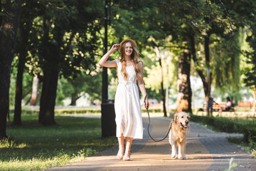 Wall Mural - full length view of beautiful girl in white dress and straw hat walking with golden retriever on pathway and looking away