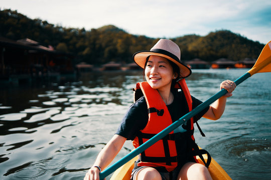 Asian girl is kayaking at Kanchanaburi, Thailand.