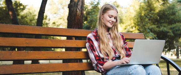 Wall Mural - panoramic shot of beautiful girl in casual clothes sitting on wooden bench in park and using laptop