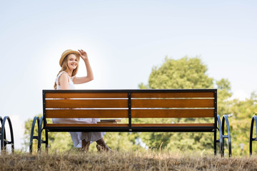 Wall Mural - beautiful girl in white dress touching straw hat and smiling while sitting on bench and looking at camera