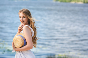 Wall Mural - beautiful young girl standing on shore of river while holding straw hat and looking at camera