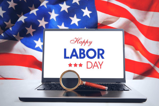 Magnifier and laptop with Happy Labor Day text