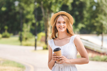 Wall Mural - beautiful girl in white dress and straw hat holding paper cup, smiling and looking away