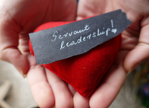 Servant leadership  note with red heart and hands