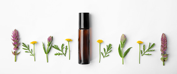 Bottle of essential oil and wildflowers on white background, top view