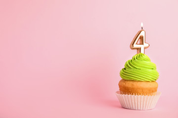 Birthday cupcake with number four candle on pink background, space for text