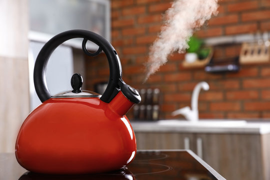 Modern kettle with whistle on stove in kitchen, space for text